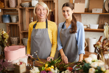 Waist up portrait of two female florists smiling at camera while arranging flowers and posing in flower shop