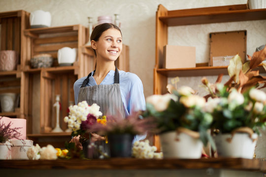 Waist up portrait of smiling young woman looking away while working in flower shop, copy space
