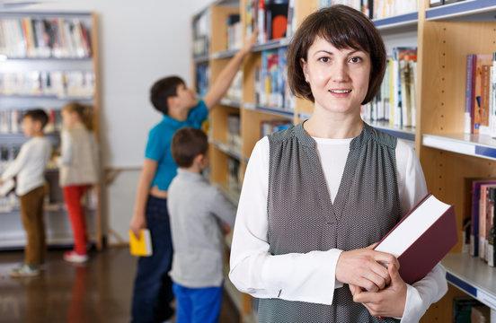 Female librarian near bookshelves