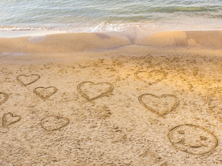 Symbols of the hearts and round face drawing on the sand on the beach of Tel Baruch . Tel Aviv Promenade. Israel