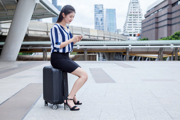 asian young business woman sitting on luggage  using smartphone .