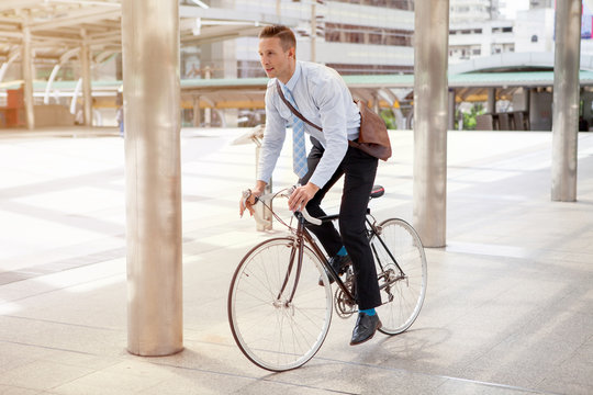 Businessman riding bicycle to work on urban street in morning .transport and healthy