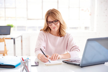 Middle aged businesswoman sitting at office desk and working on business plan