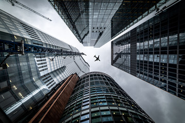 Photo sur Plexiglas Londres Silhouette of a jet plane flying low over Three different kind of architecture with commercial office buildings exterior in London
