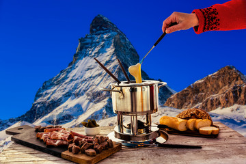 Wall Mural - Fondue cheese, swiss winter ski holidays break for lunch, mountain view Matterhorn in Zermatt, Switzerland.