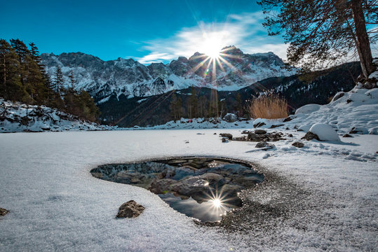 The wonderful Eibsee (lake Eibsee) in Bavaria, Germany, with ice and snow - the mountain Zugspitze is in the back with clouds and the sun