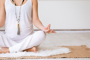 Healthy pregnancy lifestyle concept. Pregnant woman meditating in yoga lotus position, sitting on exercise mat with legs crossed and hands on knees in mudra.