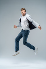 Full-length photo of funny man in casual t-shirt, blazer and jeans running or jumping in air isolated over gray background.