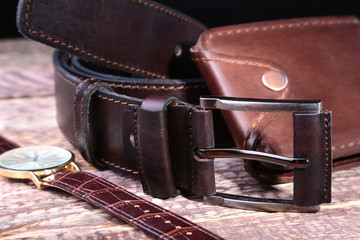 Watch, leather belt and wallet, bottle with cologne on wooden background. Stylish mens business accessories.