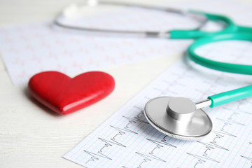 Stethoscope, red heart and cardiogram on wooden table. Cardiology concept
