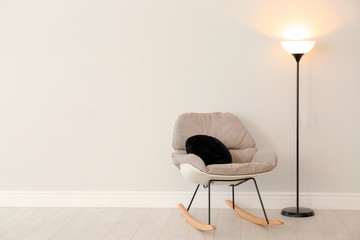 Modern floor lamp and rocking chair against light wall indoors. Space for text