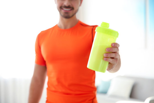 Young sporty man with bottle of protein shake at home, closeup