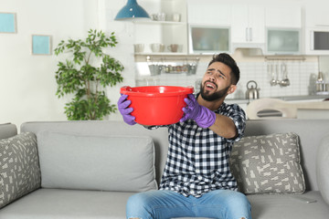 Young man holding plastic basin under water leakage from ceiling at home. Plumber service