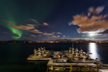 Amazing landscape view with northern lights in background at Lofoten, Norway and fish boat port in front.