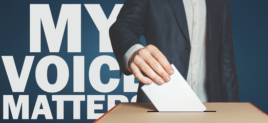My voice matters concept. Male voter holds hand a ballot above the ballot box