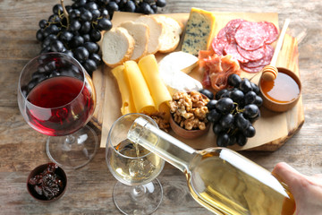 Woman pouring white wine into glass on table with delicious food, closeup