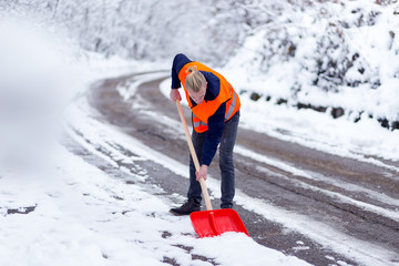 Man in reflective west using shovel to cleaning snow