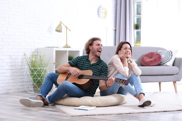 Young man playing acoustic guitar badly for displeased girlfriend in living room. Talentless musician