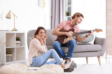Young man playing electric guitar badly for displeased girlfriend in living room. Talentless musician