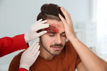 Nurse examining young man's head injury in clinic. First aid