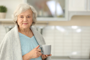 Elderly woman with cup of tea in kitchen. Space for text