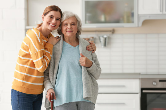 Elderly woman with female caregiver in kitchen. Space for text
