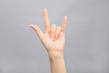 Woman showing hand sign on grey background, closeup. Body language