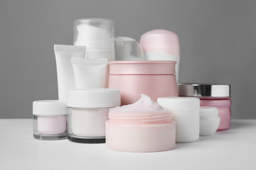 Different body care products on gray background