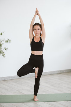 Yoga and Fitness. Young woman in Astavakrasana yoga pose at home