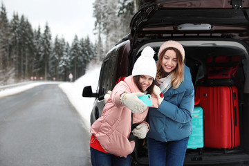 Friends taking selfie near open car trunk full of luggage on road, space for text. Winter vacation