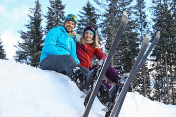 Happy couple with ski equipment sitting on snowdrift outdoors. Winter vacation