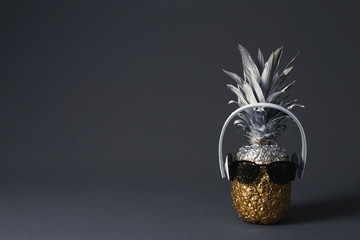 Pineapple with headphones and sunglasses on dark background. Space for text
