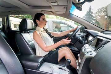 Beautiful woman sitting in driver seat inside car