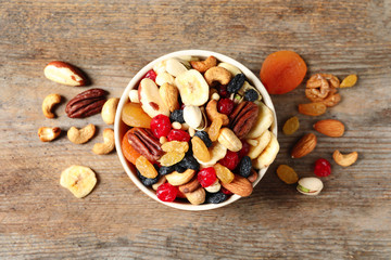 Bowl with different dried fruits and nuts on wooden background, top view.