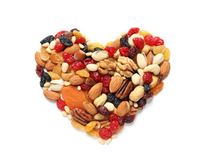 Heart made of dried fruits and nuts on white background, top view