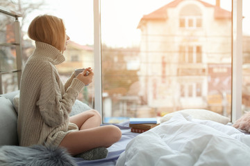 Beautiful young woman in knitted sweater sitting with cup and looking at window in room. Winter atmosphere