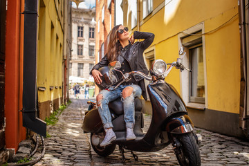 Girl in sunglasses wearing a leather jacket and ripped jeans sitting on a black classic scooter on an old narrow street.