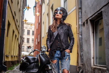 Girl in protective helmet and sunglasses wearing a leather jacket and ripped jeans standing near a black scooter on a old narrow street.