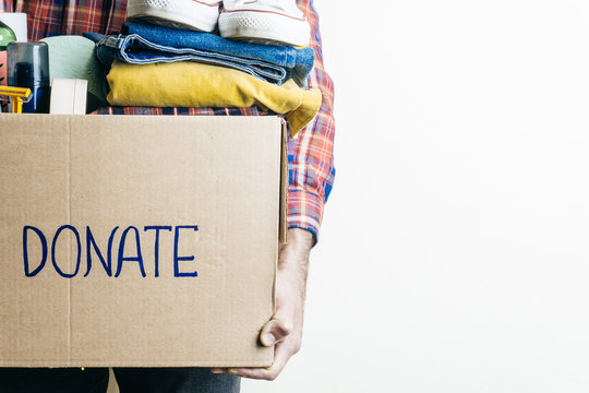 CLOTHES DONATION AND FOOD DONATION CONCEPT. A man holding a donation box with clothes, shoes and hygiene products. Copy space
