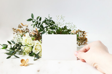 Bright feminine wedding stationery mockup scene. Closeup of woman hand holding paper place card. Bouquet of eucalyptus, dry hydrangea, white roses and gypsophila flowers on marble table background.