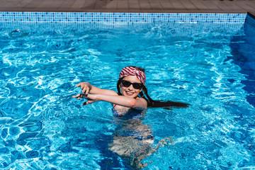 Beautiful teenage girl relaxing in pool water