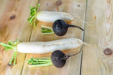 Black and white fresh organic radish on wooden desk. Flat lay, top view.