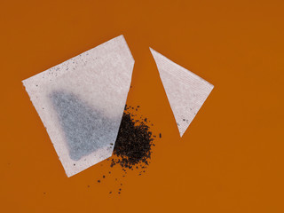 Tea bag sachet cut open to see contents and quality of leaves inside, on orange colour background.
