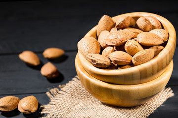 Almonds with shell in wooden bowls on slate background