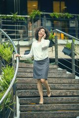 Asian woman talking on phone standing on the stairs.