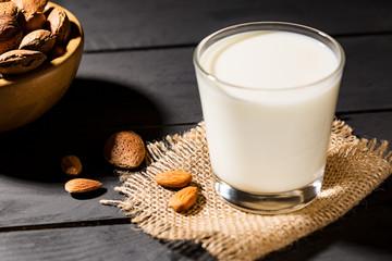 Almonds milk in wooden bowls on black background