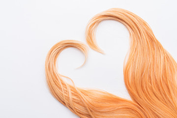 Human, natural honey-colored blond hair on white isolated background. Stylish, fashionable colors this year. Honey blonde in the shape of heart. An example of hairstyle.