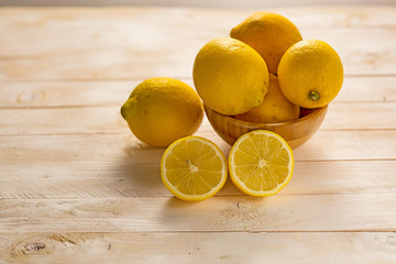 Lemon fruits in a wood bowl on a white rustic wooden table