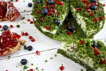 """Ciasto """"zielony mech"""" ze szpinakiem ozdobione pestkami granatu i jagodami"""