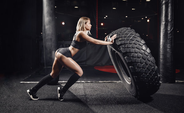 Workout fitness concept. Sports woman turns over tire wheel in gym, sweat drops, force.
